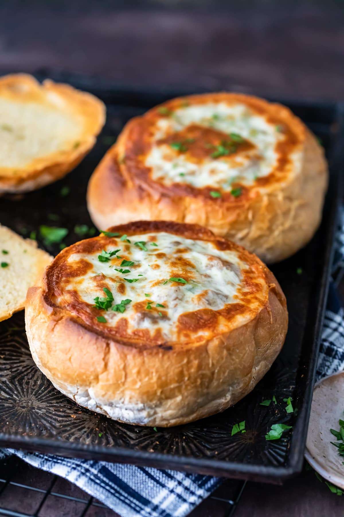 Bread bowls on a baking tray, filled with soup and topped with cheese