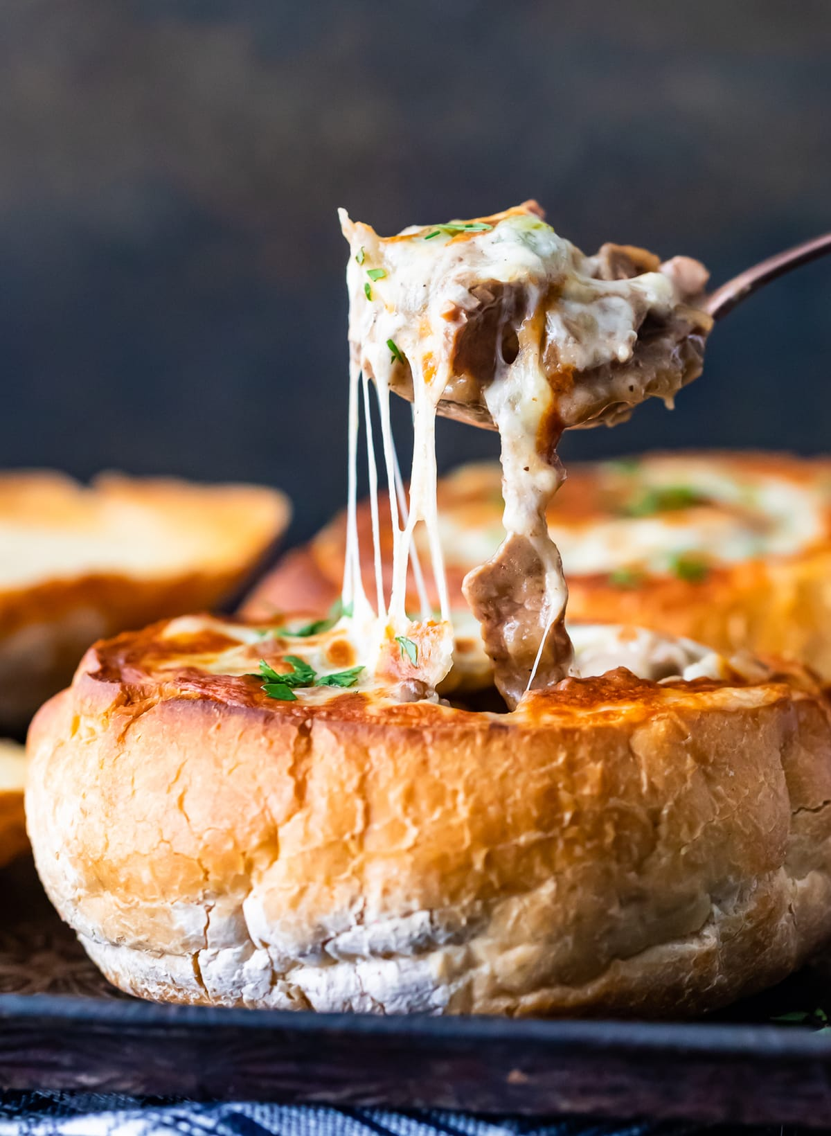 pulling a spoonful of cheesy soup out of a bread bowl