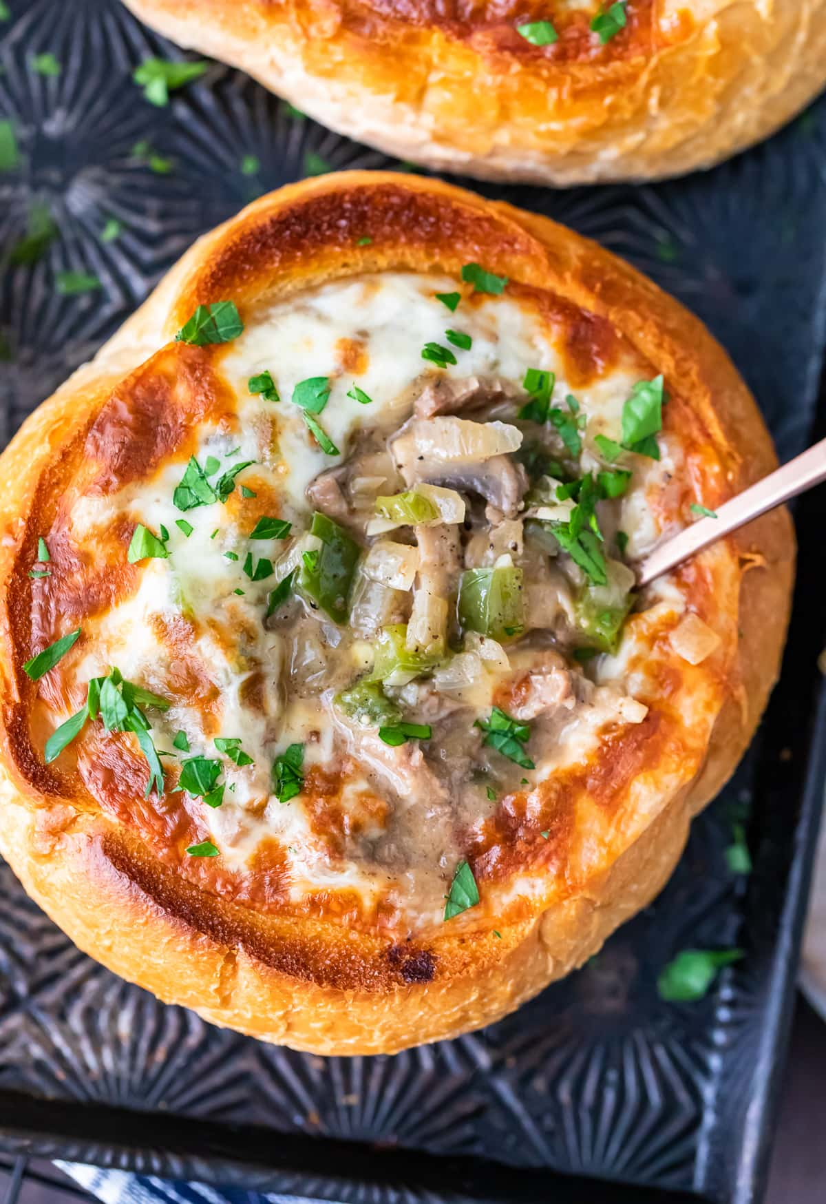 close up on a bread bowl soup filled with beef, cheese, onions, mushrooms, and green peppers