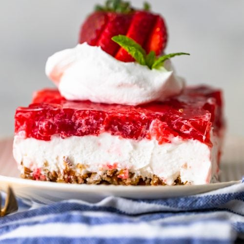 Strawberry Pretzel Salad on a plate with whipped cream and strawberries on top