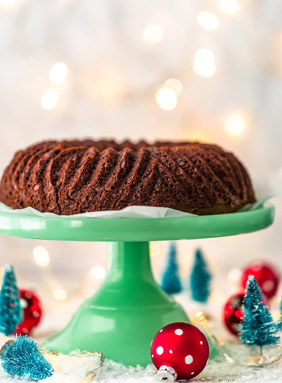 gingerbread cake on a cake stand, with mini Christmas decorations below it