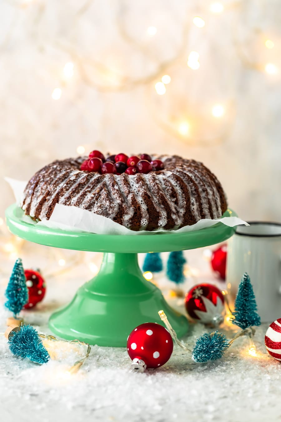 gingerbread cake on a green cake stand, surrounded by small Christmas decorations