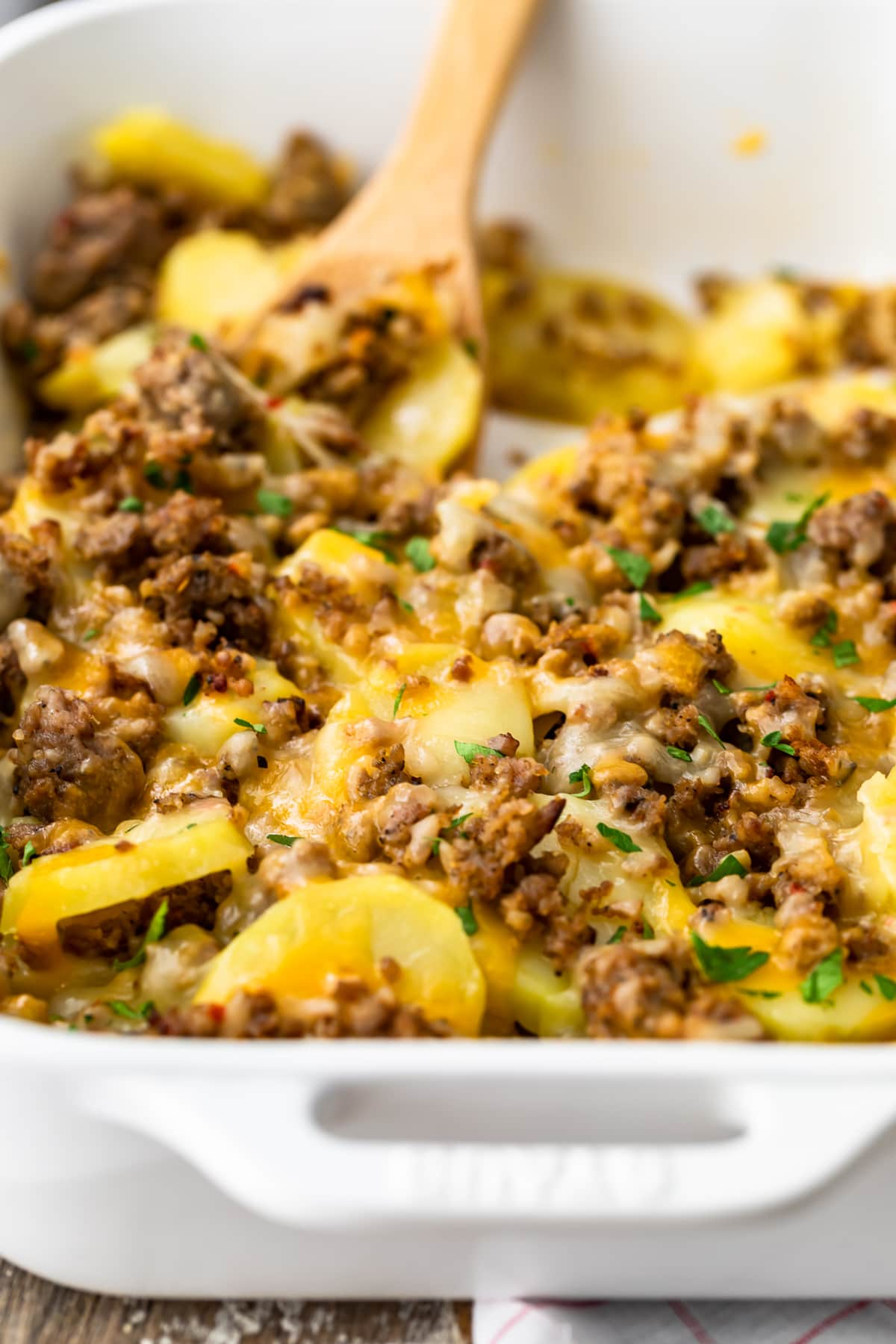 sausage and potato casserole in a white dish with a wooden spoon