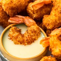 Coconut Shrimp is a crispy, crave-worthy appetizer that everyone will love. It's especially delicious when paired with the perfect coconut shrimp sauce: a Spicy Pina Colada Dipping Sauce! The two go hand in hand, a match made in heaven. And this coconut shrimp recipe is just as good as a main dish as it is as a party appetizer!