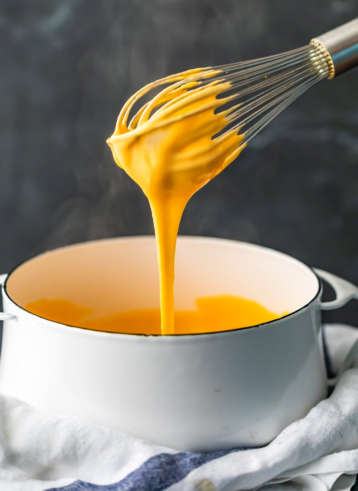 a whisk covered in cheese sauce