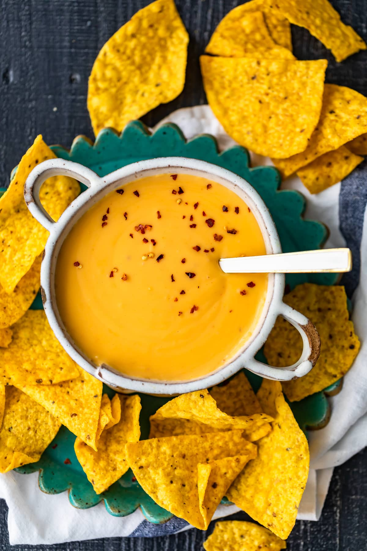 homemade nacho cheese sauce in a bowl, surrounded by tortilla chips
