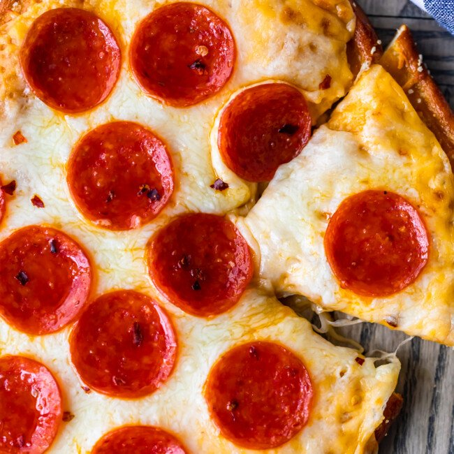 Soft Pretzel Crust Pizza with Cheese Sauce is the ULTIMATE easy Cheesy Pizza Recipe! This pizza is a Little Caesar's Copycat Recipe, modeled after their famous Pretzel Crust Pizza Recipe with cheese sauce instead of marinara! We are obsessed!