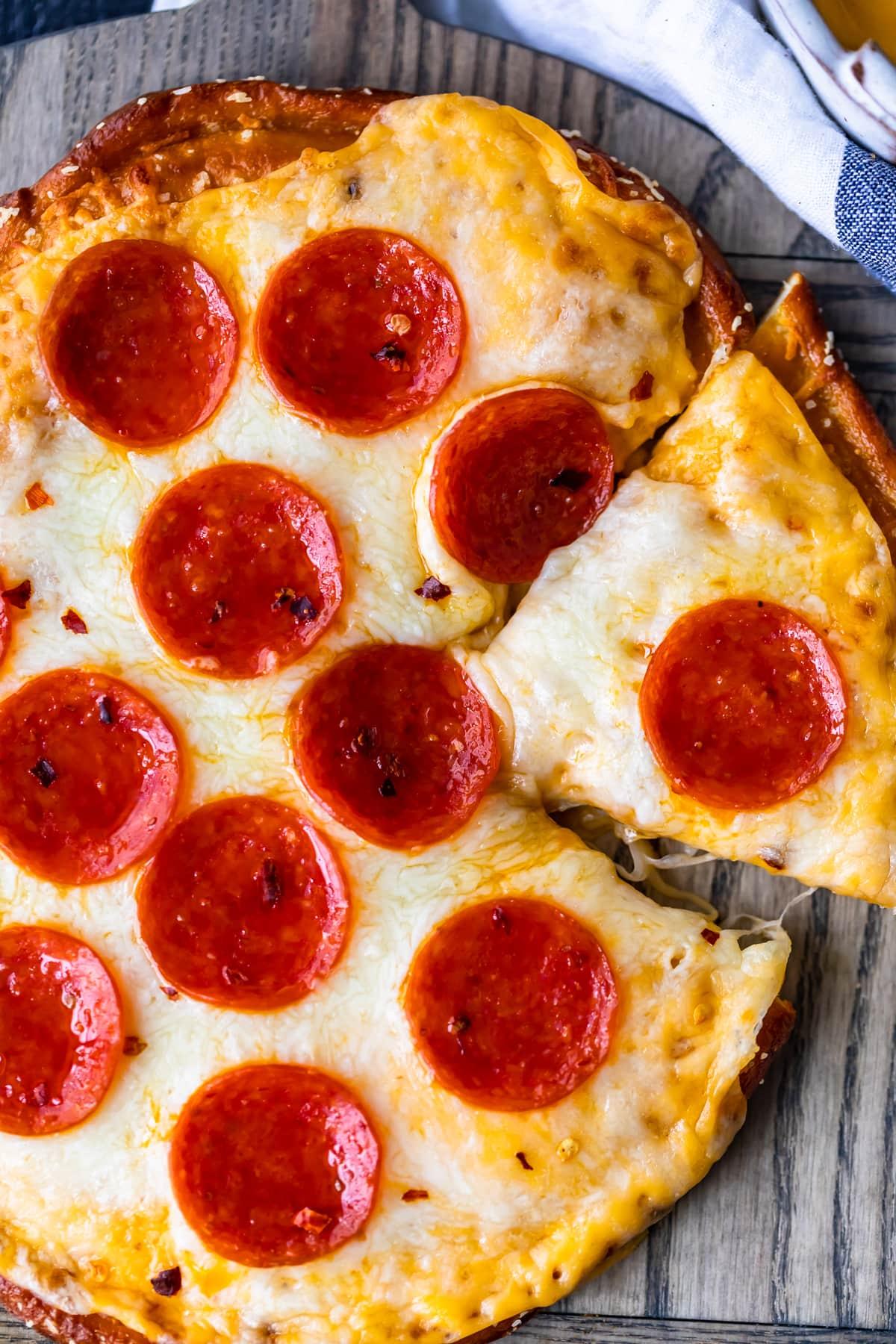 overhead shot of piece cut out of soft pretzel crust pizza with pepperoni little caesar's copycat recipe