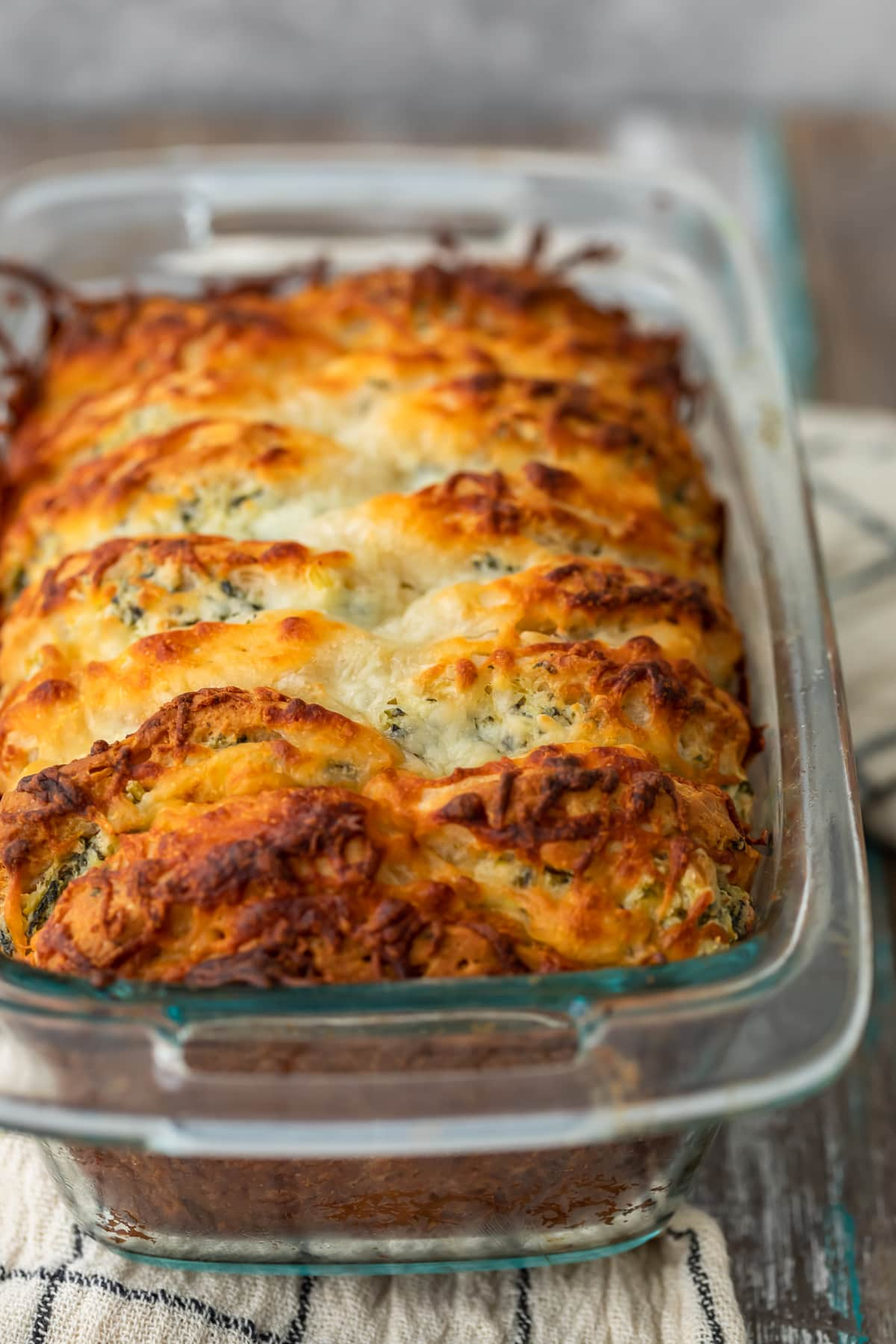 loaf of pull apart bread in a bread pan, topped with cheese and parsley butter