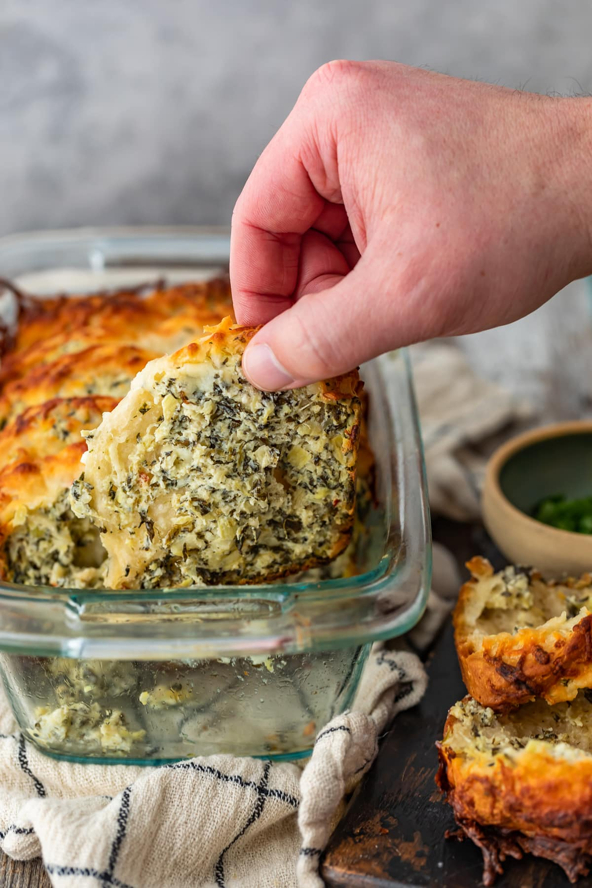 pulling a piece of spinach artichoke dip bread out of a glass loaf pan