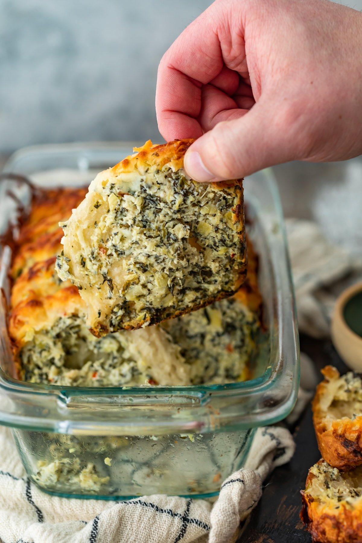 hand pulling a piece of spinach artichoke bread out of a glass dish