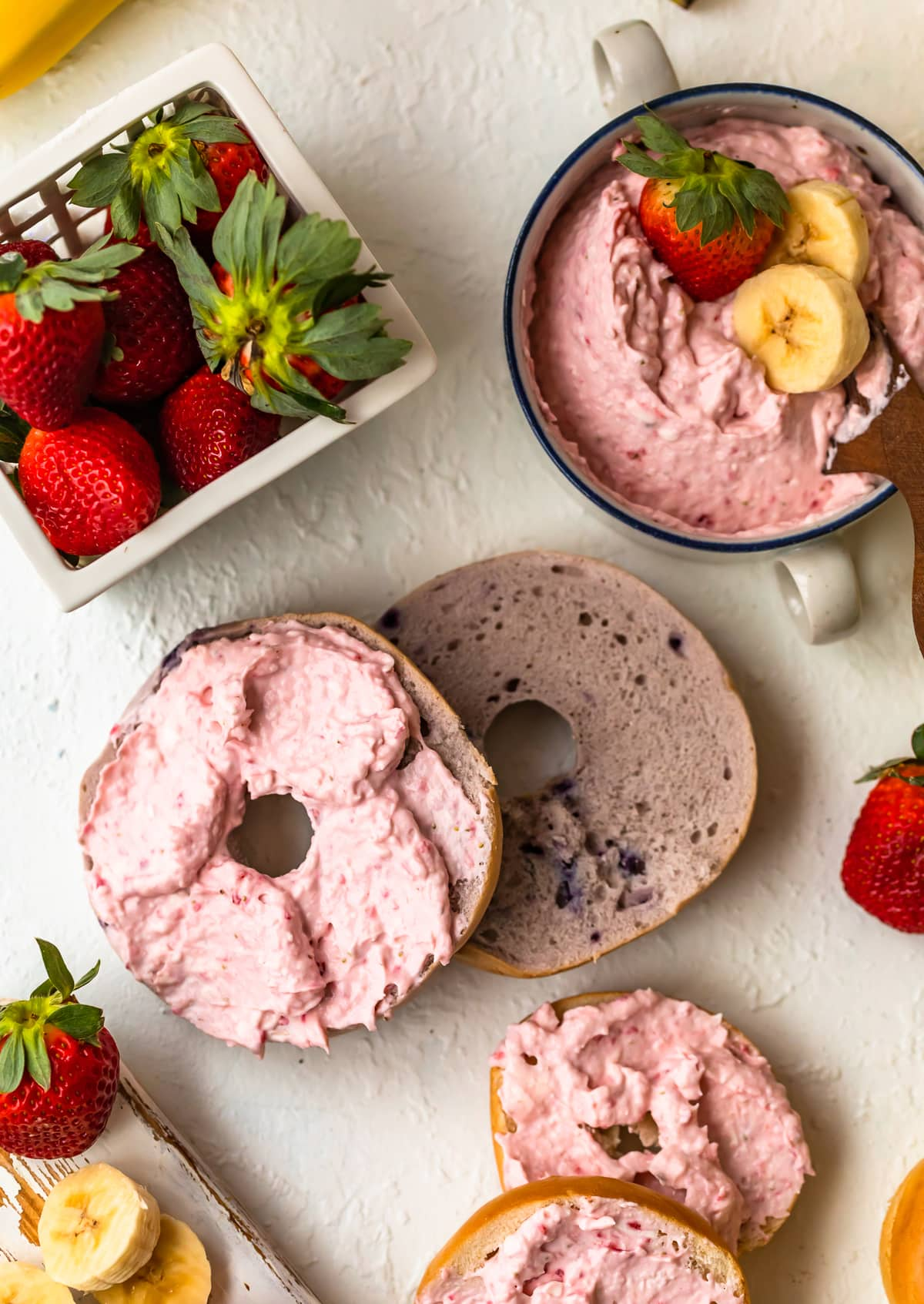 a bagel with cream cheese next to a basket of strawberries and a bowl of strawberry cream cheese