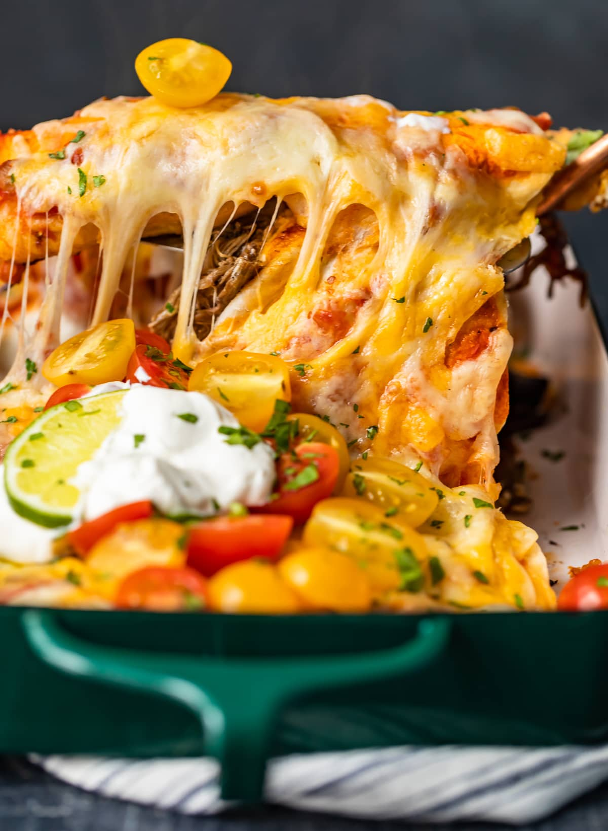 cheesy beef enchiladas in a green casserole dish
