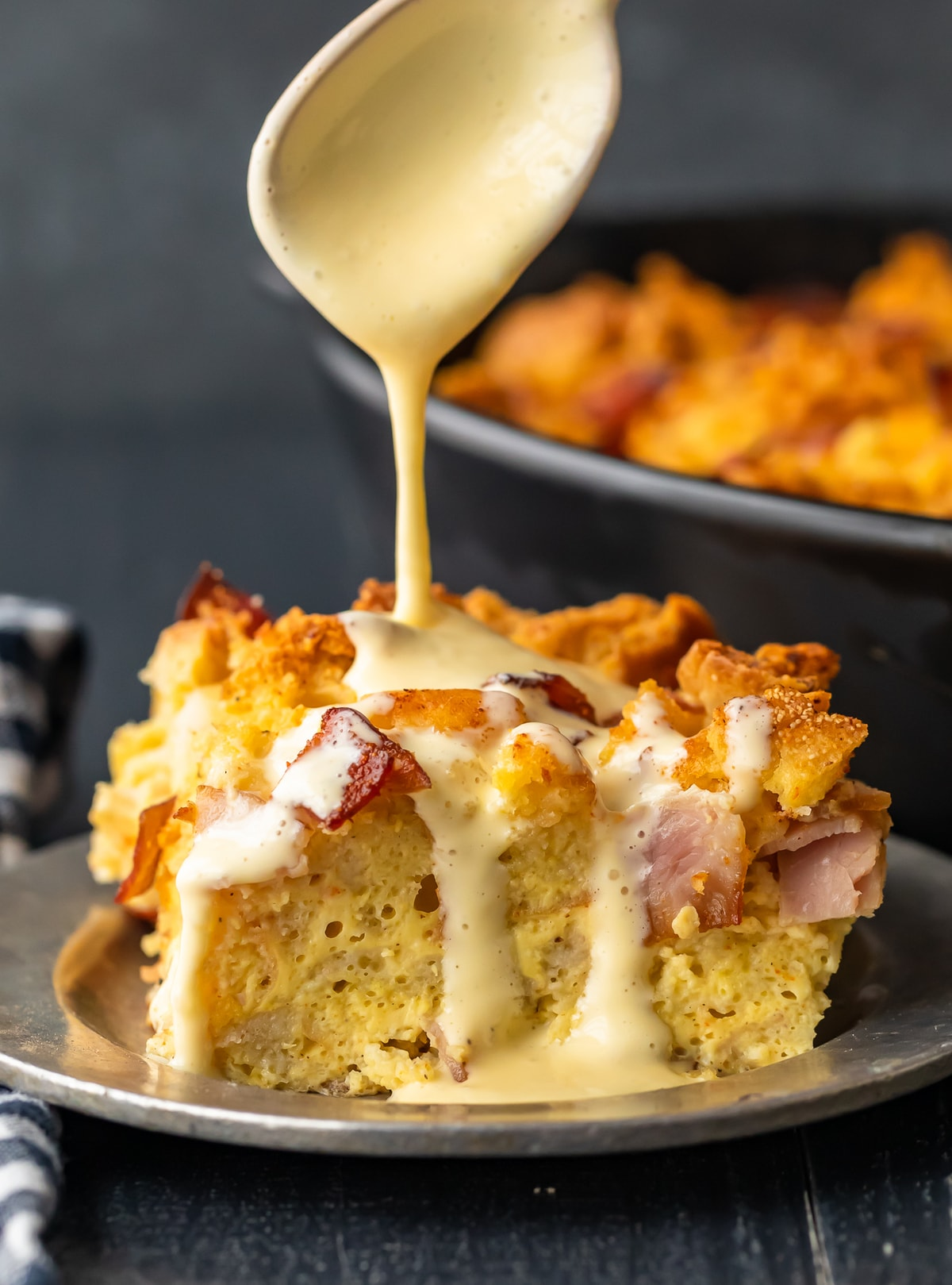 eggs benedict casserole topped with hollandaise sauce