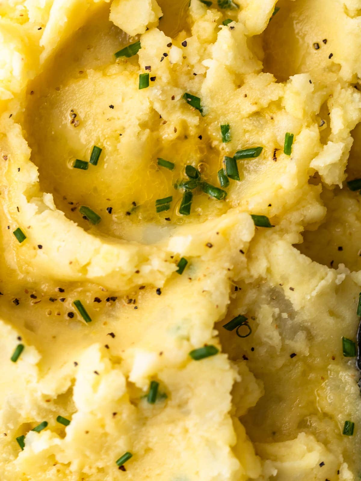 close up on creamy mashed potatoes topped with chives