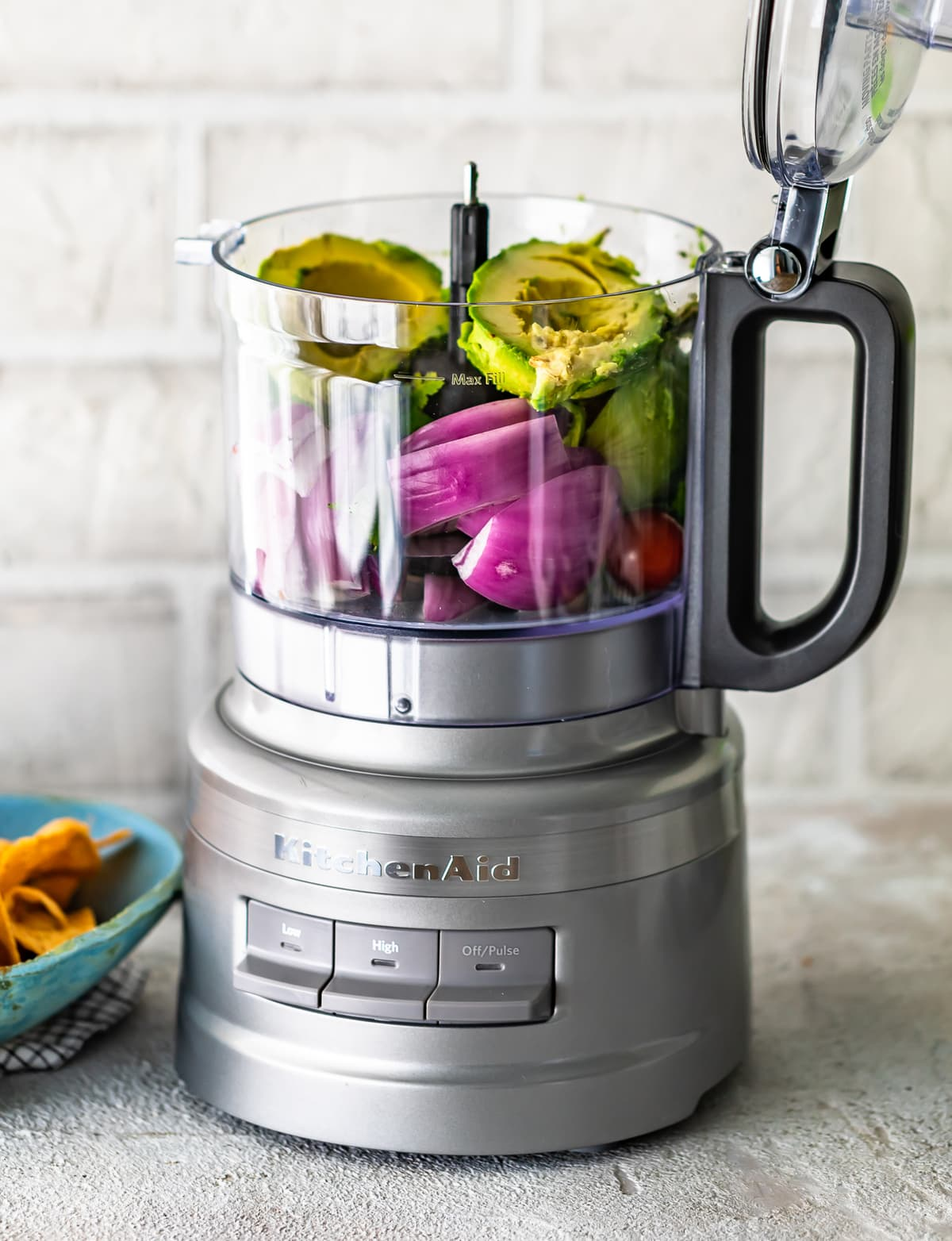 food processor filled with guacamole ingredients