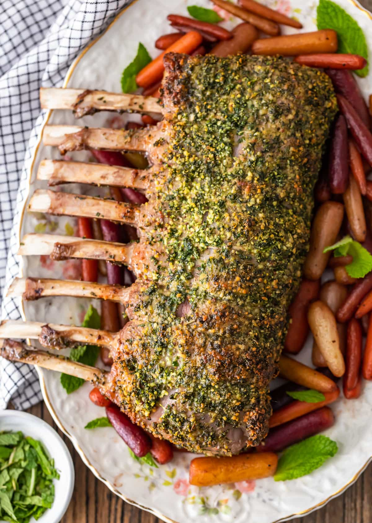 herb crusted rack of lamb on a palte with roasted carrots