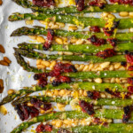 Oven Roasted Asparagus with sun dried tomatoes, pine nuts, garlic, and more is a delicious Mediterranean-inspired side dish fit for any occasion. This easy roasted asparagus recipe is quick to make yet filled with flavor! Add this asparagus side dish to your holiday meals, or just to your weeknight dinners. Either way, it's sure to be a hit!