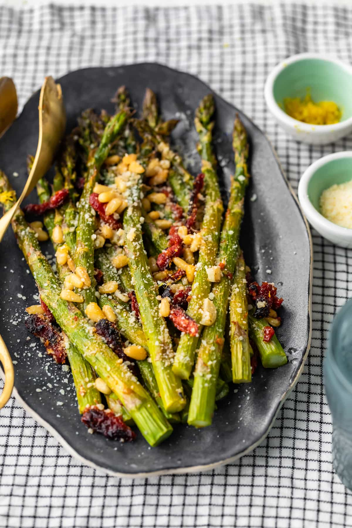 a plate of asparagus mixed with sun dried tomatoes, pine nuts, and more