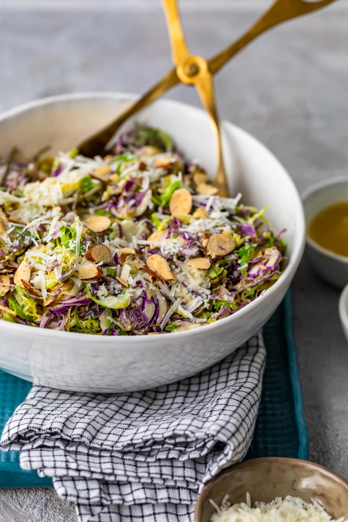 brussels sprouts salad in a white bowl with gold tongs