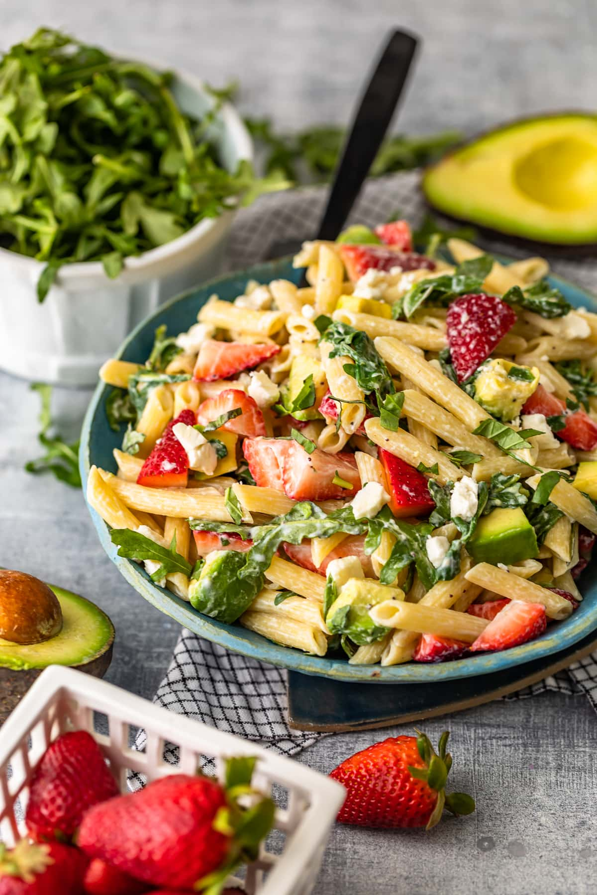 bowl of pasta salad surrounded by avocados, strawberries, and arugula