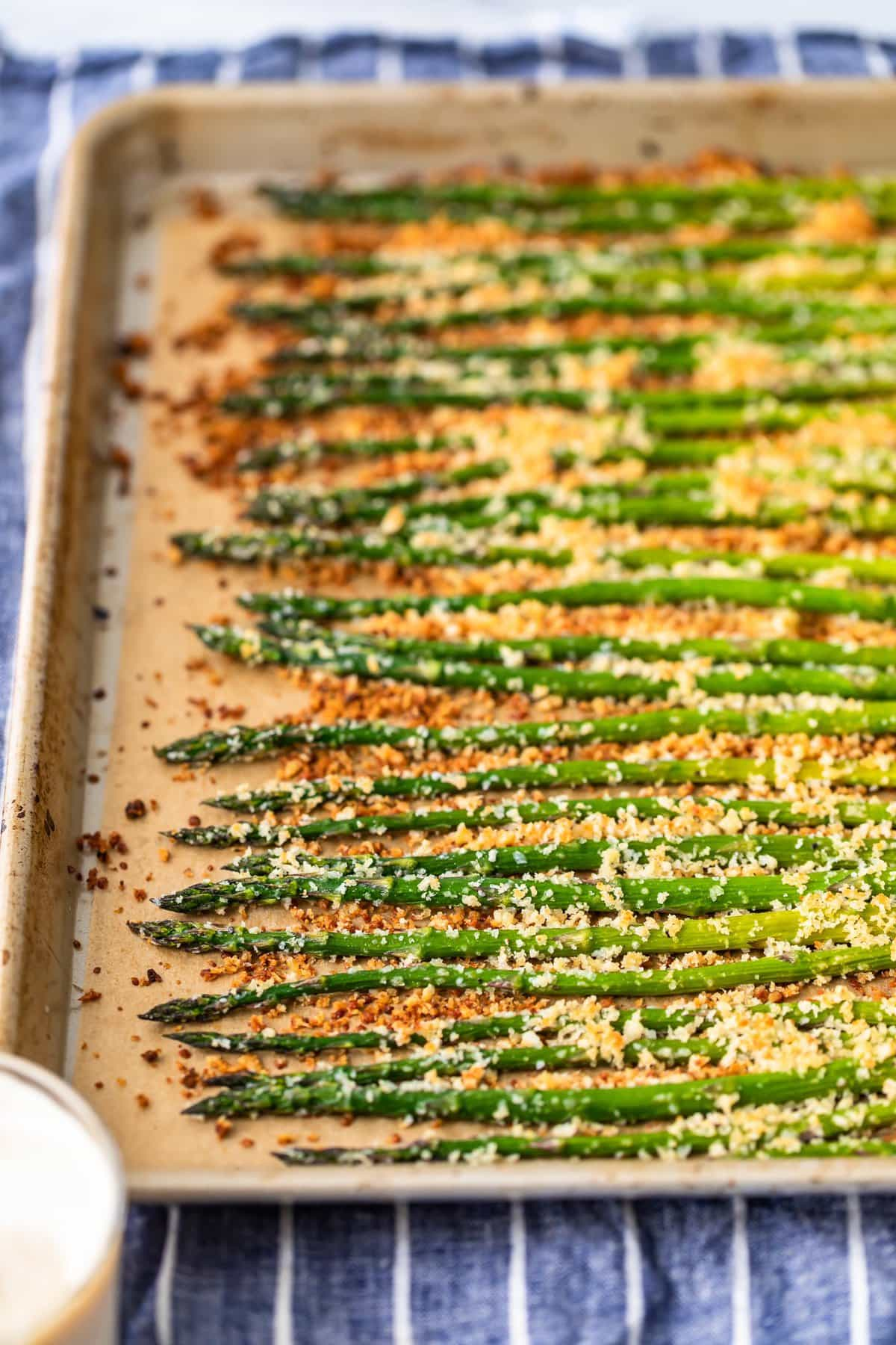 asparagus lined up on a baking tray