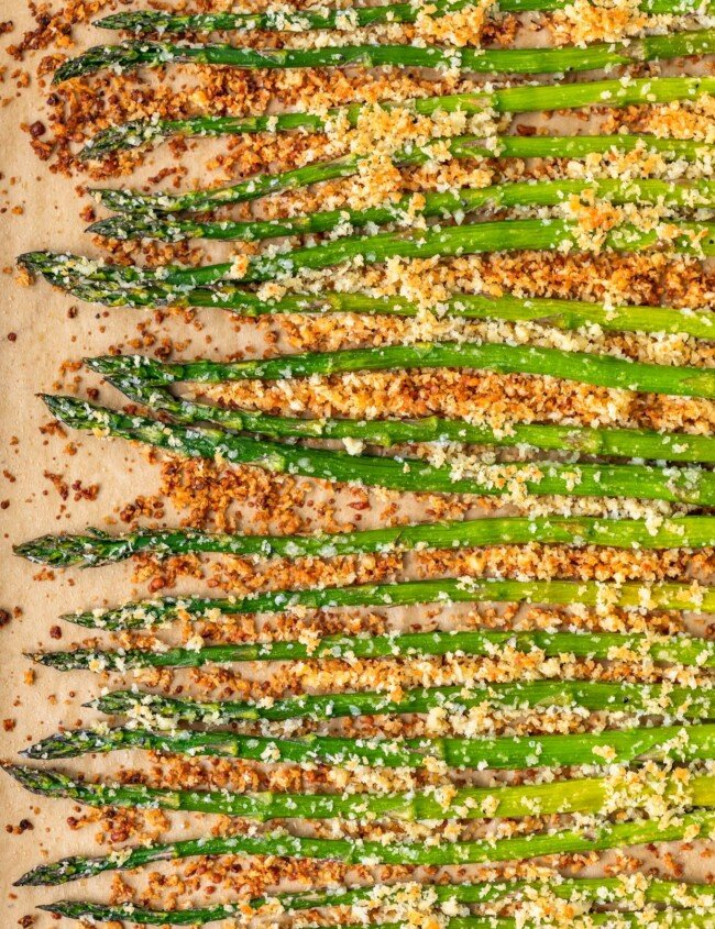 Garlic Asparagus is an easy side dish for any meal. This CRISPY garlic roasted asparagus recipe is both healthy and flavorful. Baked with panko breadcrumbs, garlic, cheese, and olive oil, this is a dish everyone is sure to love. If that's not enough, our garlic parmesan asparagus is topped off with homemade garlic aioli!