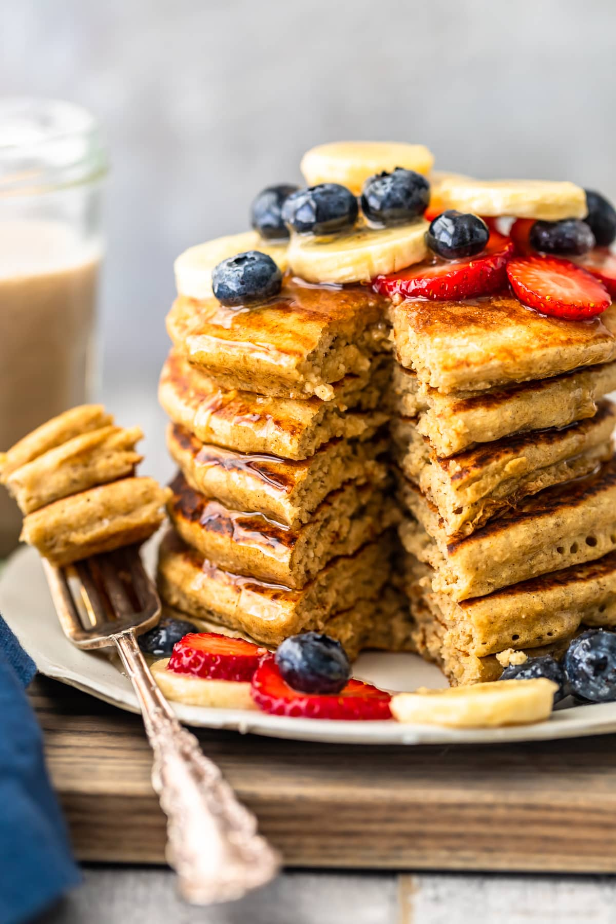 banana pancakes stacked on a plate with bite cut out