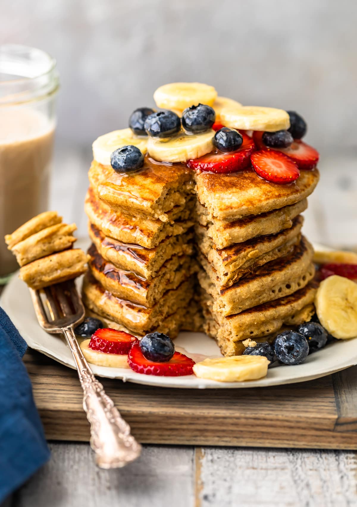 easy banana pancakes recipe with fresh fruit and honey with bite cut out