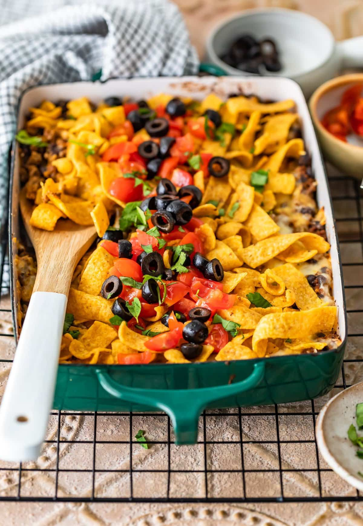 casserole dish filled with corn chips, beef, cheese, and more