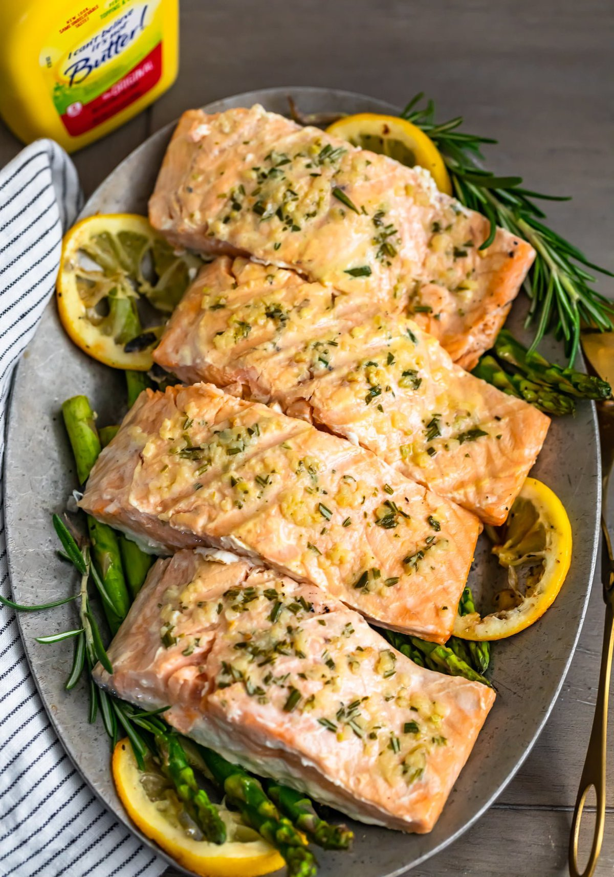 garlic lemon butter salmon on a plate of asparagus