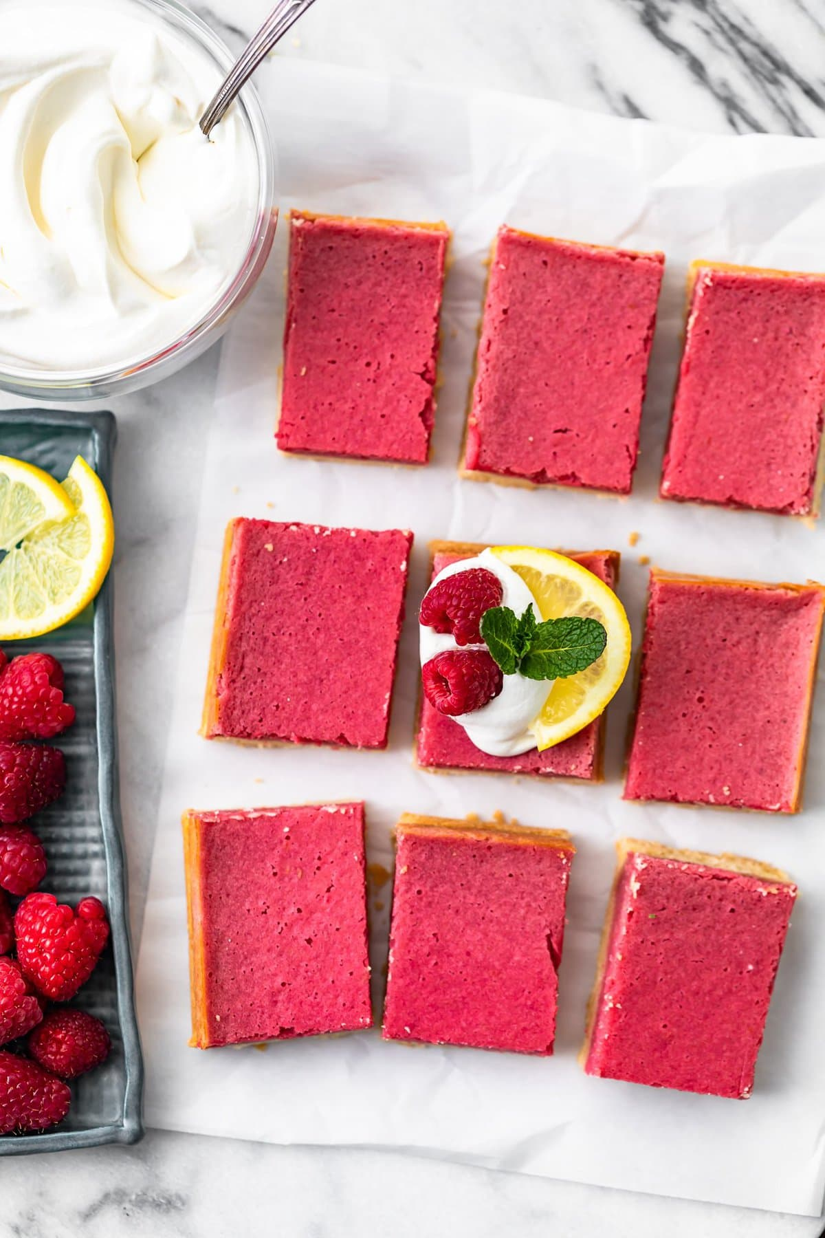 raspberry bars arranged on a sheet of parchment paper