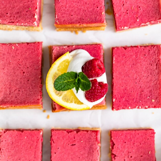 Raspberry Bars are a delicious and easy dessert to serve for any holiday, party, or summer afternoon. These fruity Raspberry Lemon Bars have the perfect flavor, the perfect texture, and the perfect pink color. Top them with some fresh fruit, powdered sugar, and whipped cream for a delightful treat!