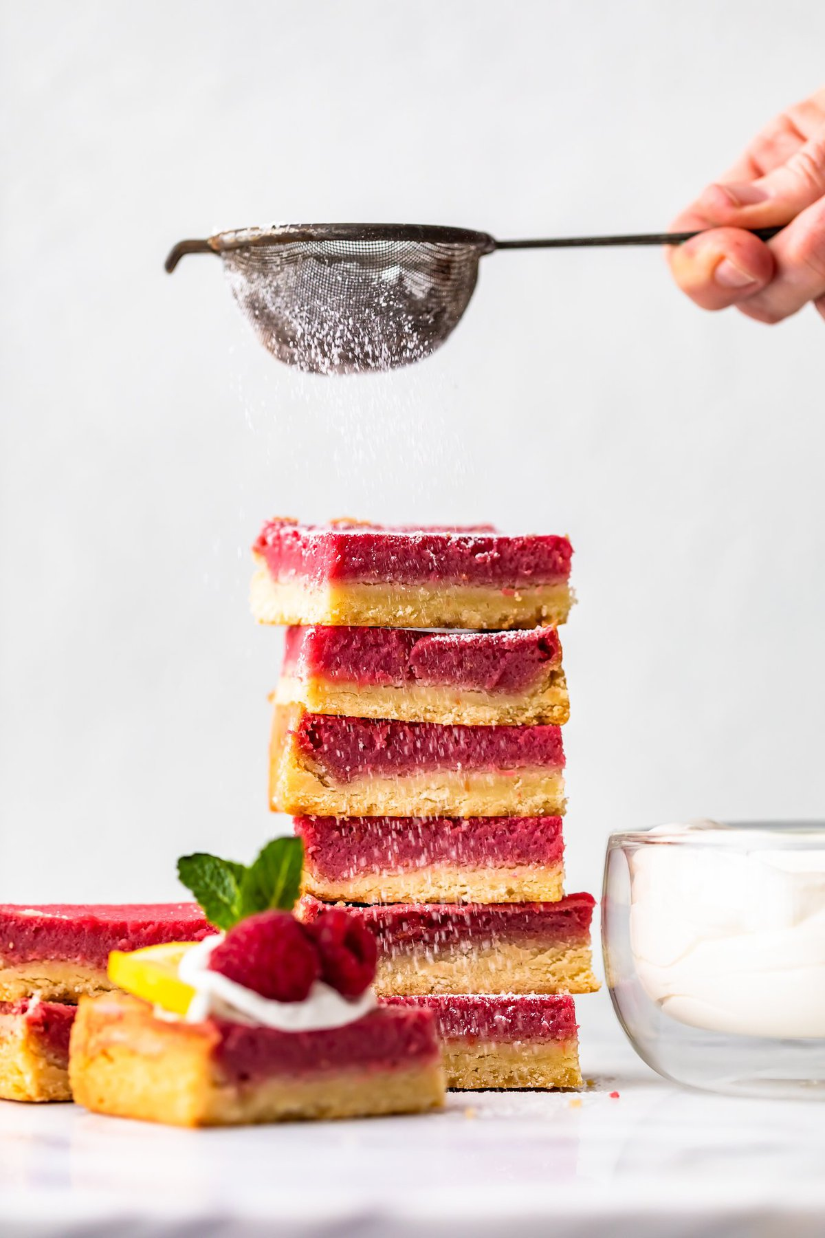 sprinkling powdered sugar over a stack of raspberry bars