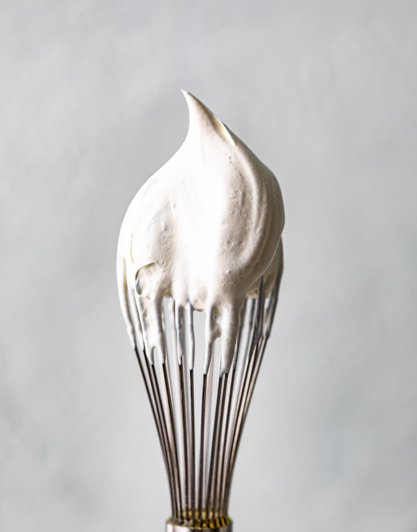 a whisk dipped in whipped cream