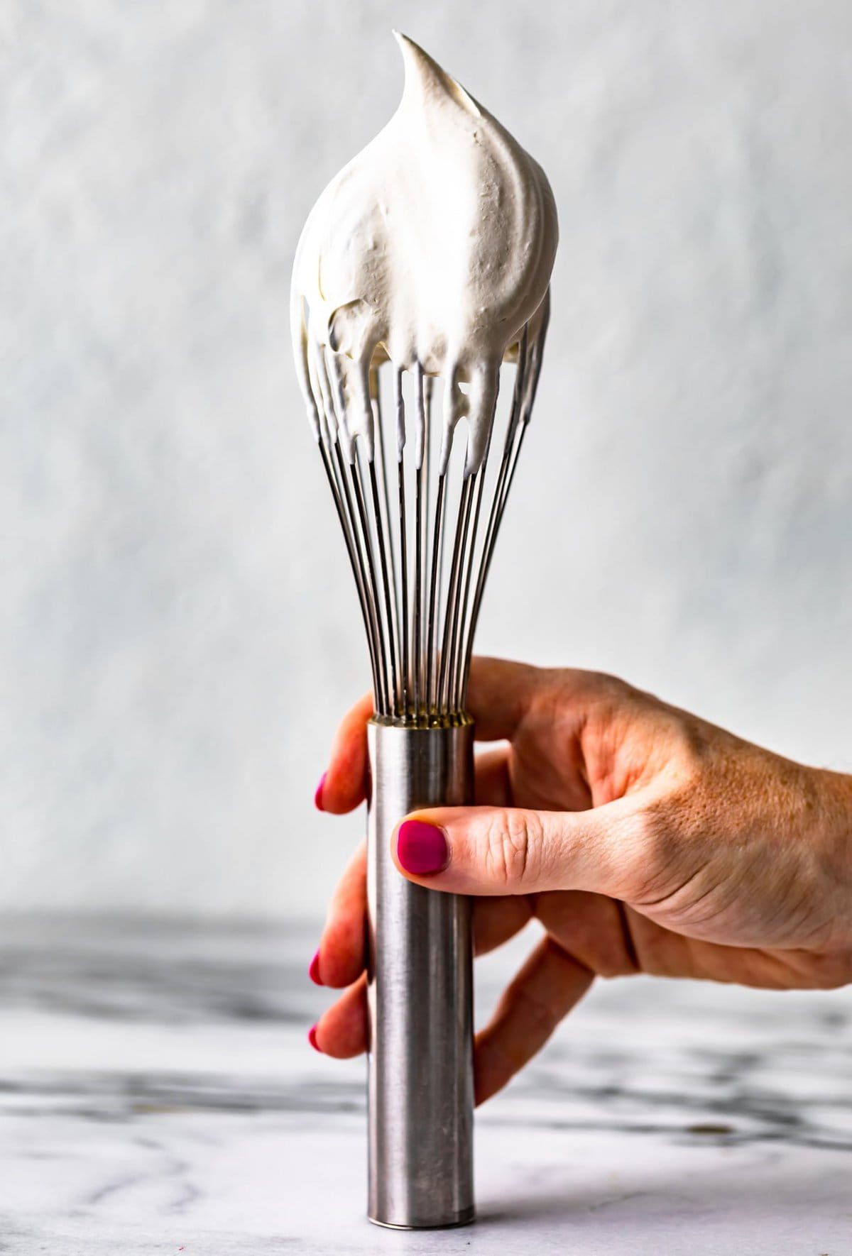 hand holding a whisk dipped in whipped cream