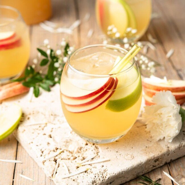 An apple pie drink in a round glass with slices of apple and a straw