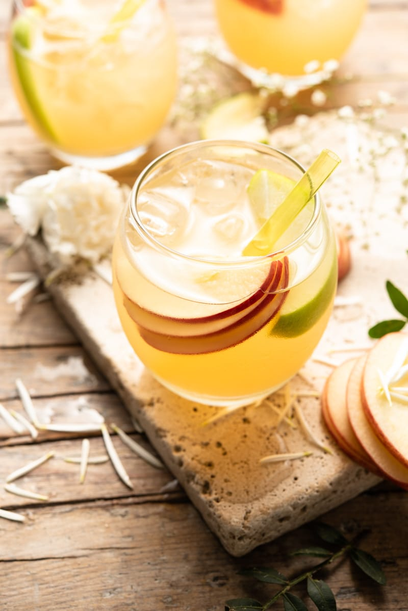 A close up of an apple pie drink in a round glass with slices of apple and a yellow straw