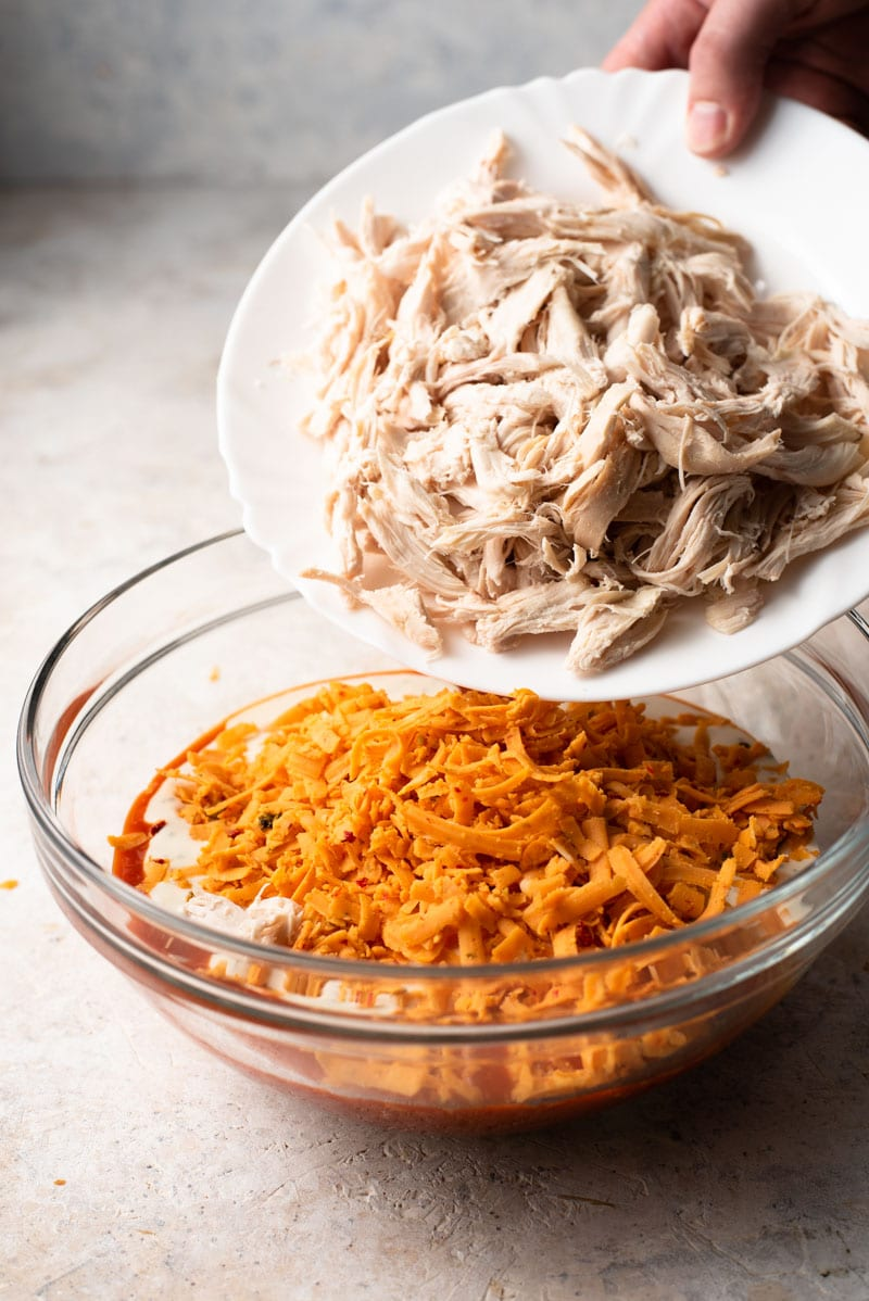 Shredded chicken in a bowl to make buffalo chicken dip