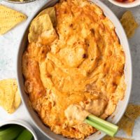 buffalo chicken dip in white baking dish with celery stalk dipped in it