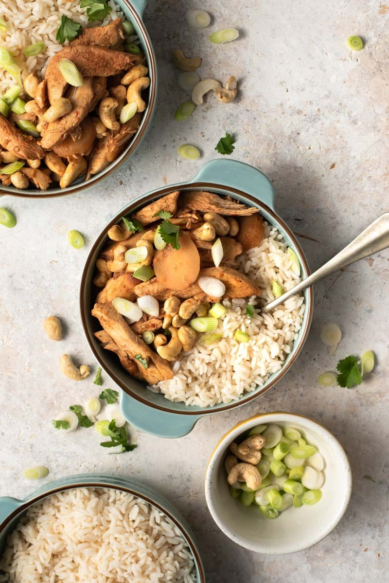 An overhead shot of cashew chicken in blue bowls with rice
