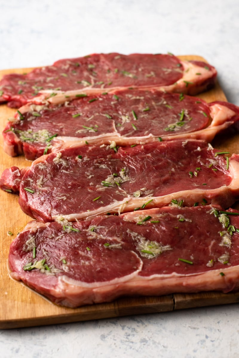 Four New York Strip Steaks on a cutting board