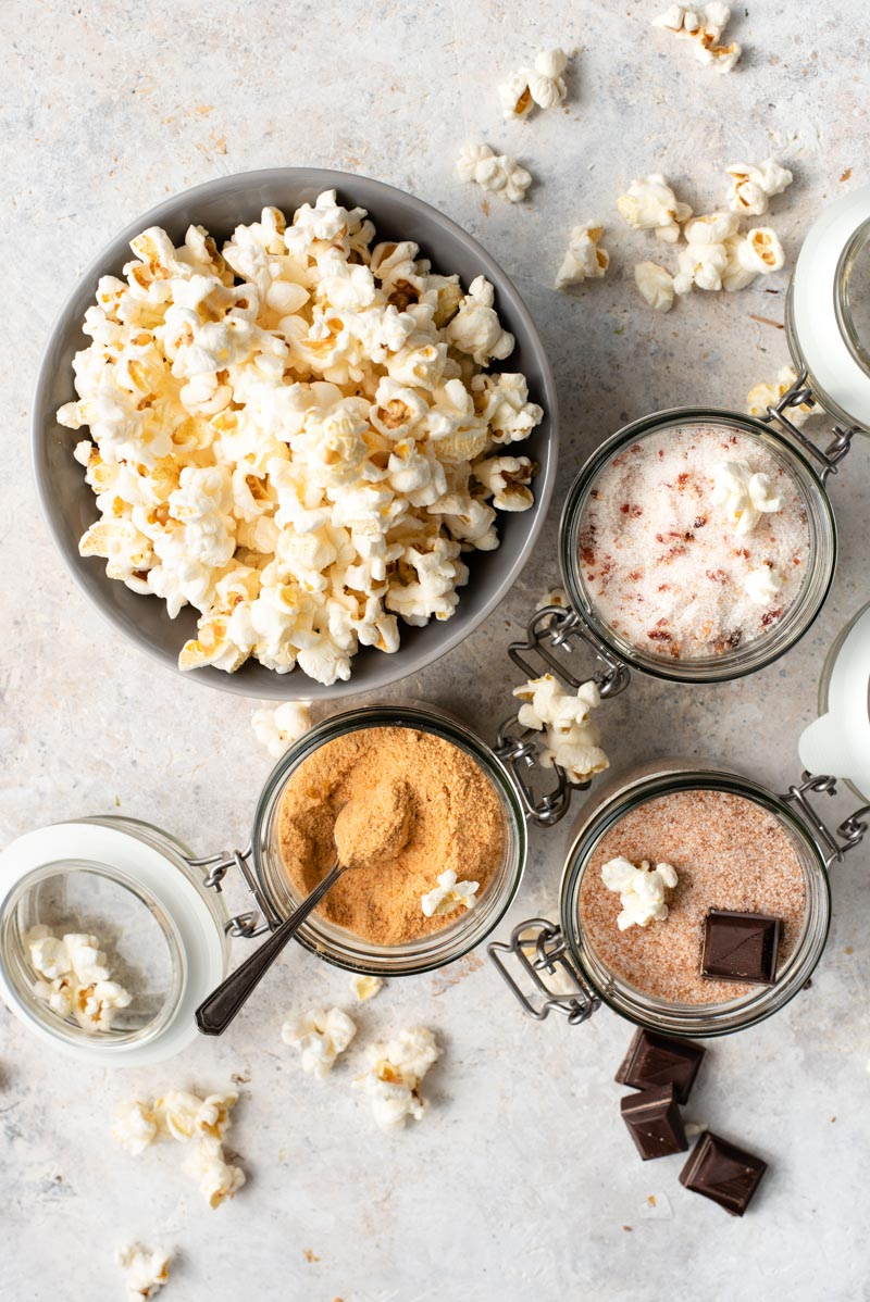 over the top shot of popcorn in a bowl surrounded by different powdered ingredients in jars