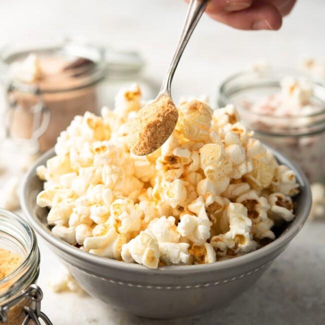 popcorn salt on a spoon above a bowl of popcorn