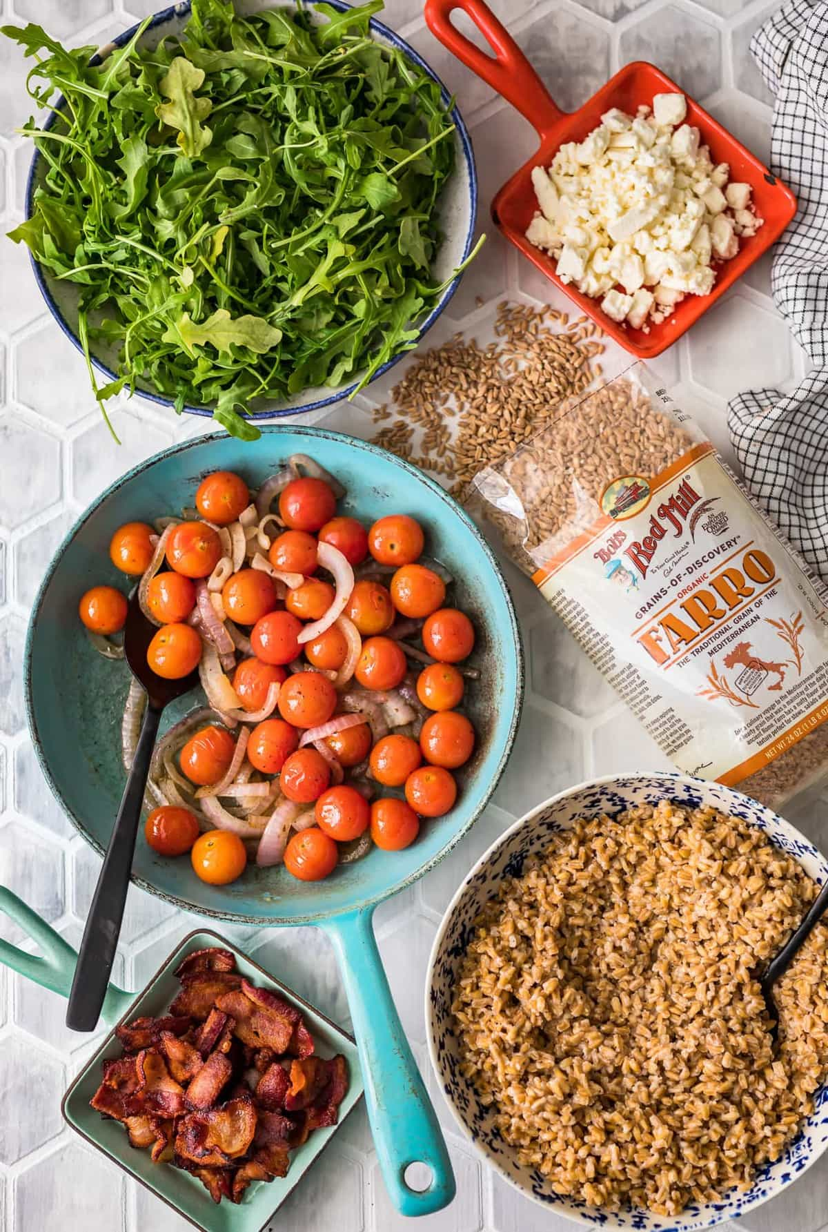 bowls of tomatoes, arugula, and farro arranged on a table