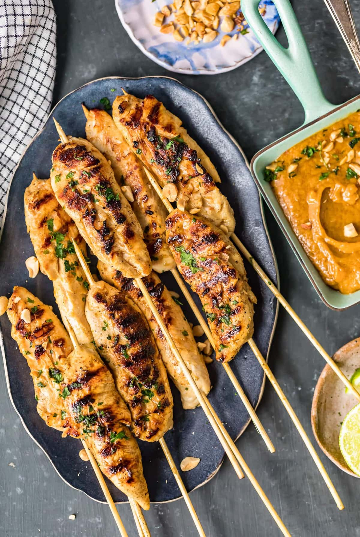chicken skewers on a plate next to a bowl of peanut sauce