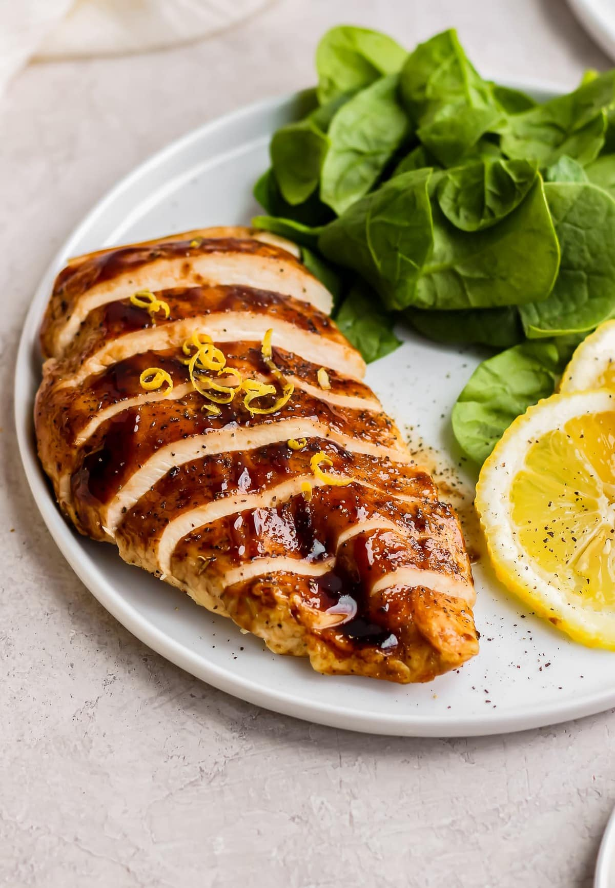 sliced honey balsamic chicken with spinach and lemon