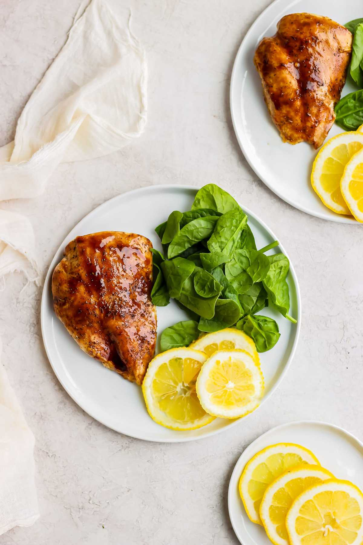 plate of chicken, spinach, and lemon slices