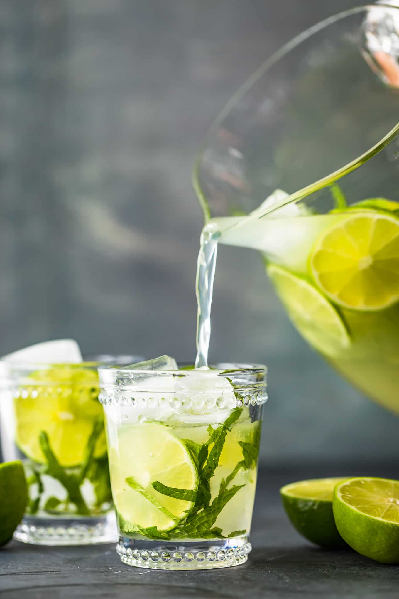 pouring mojitos into glasses