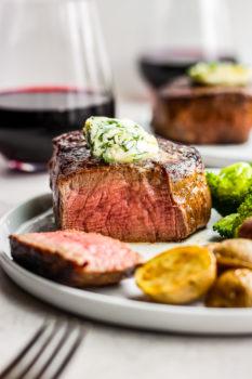 sliced steak with cilantro steak butter on top